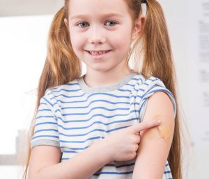 cheerful girl getting a vaccination - image links to information about flu shots